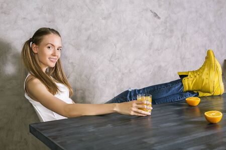 beautiful feet: Pretty european girl with ponytails sitting at wooden desk with oranges and juice and her feet up high