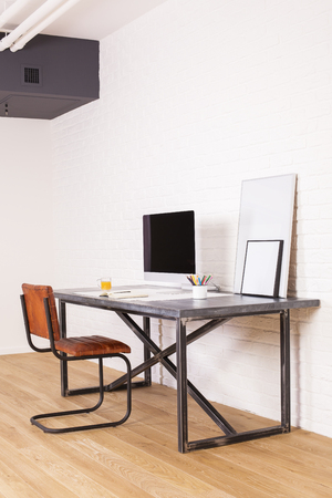 designer chair: Sideview of brown chair and designer desk with computer monitor and picture frames on wooden floor and white brick wall background