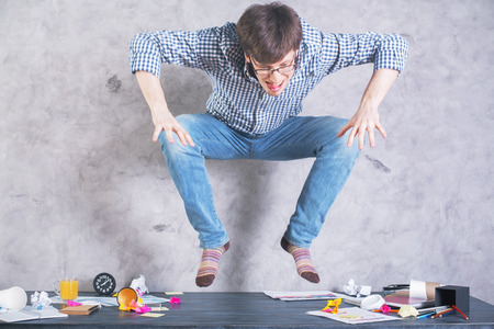 going crazy: Young caucasian male jumping on messy wooden desktop with concrete wall in the background