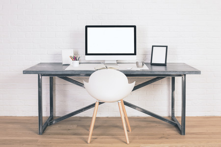 designer chair: Front view of designer desk with blank white computer screen, frames and other items with white chair next to it. Wooden floor and white brick wall background. Mock up