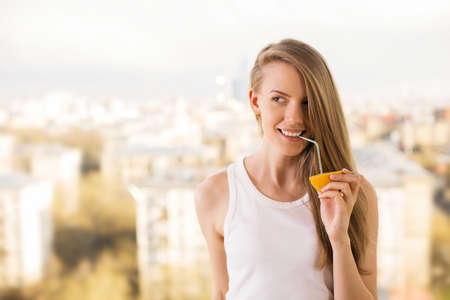 tomando jugo: niña de beber jugo de media naranja sonriente con una paja en el fondo borroso de la ciudad