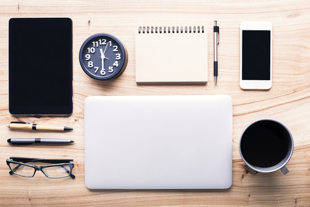organized office: Topview of wooden desktop with neatly organized office tools and electronic gadgets. Mock up Stock Photo