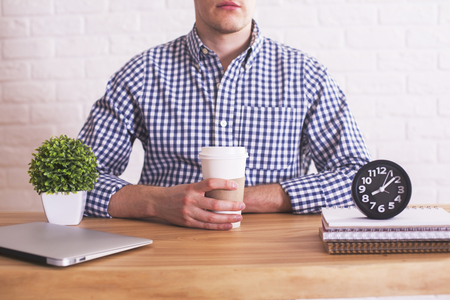 laptop computer: Young caucasian guy with coffee cup in hands sitting at wooden desk with closed laptop, plant and clock. White brick wall in the background Stock Photo
