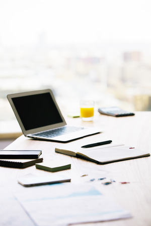 sideview: Office desktop with blank laptop screen, orange juice and various office tools. Blurry background Stock Photo