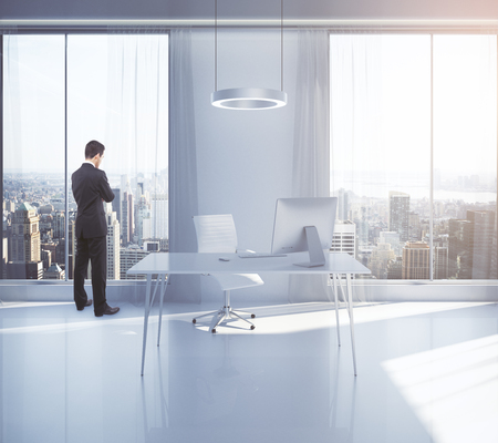 executive apartment: Thoughtful businessman looking outside of window in office interior with workplace and New York city view. 3D Rendering Stock Photo