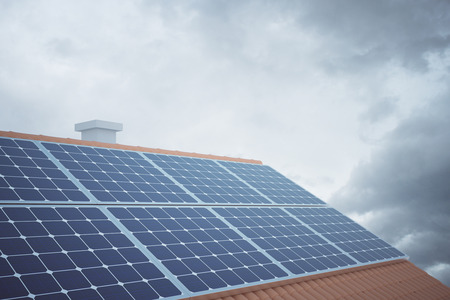 panels: Side view of solar panels on house roof against cloudy sky. 3D Rendering Stock Photo