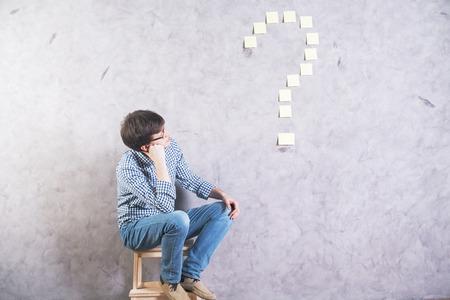 hombre caucásico pensativo sentado al lado y mirando en la etiqueta de signo de interrogación pegado a la pared de hormigón