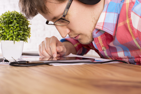 closely: Closeup of caucasian male with headphones on, very closely looking at tablet, placed on wooden table with small plant Stock Photo
