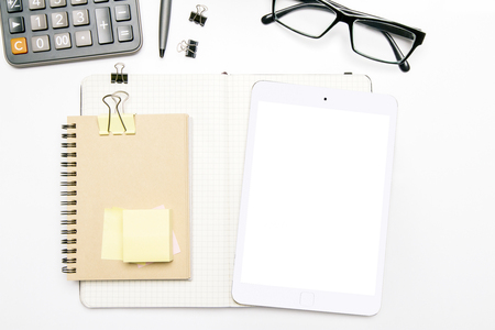 Topview of white desk with blank tablet screen, notepad with clips glasses and other items. Mock up Stock Photo