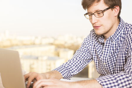 sideview: Sideview of young caucasian male typing on laptop keyboard with blurry city in the background