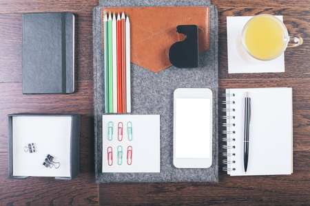 neatly: Top view of wooden tabletop with neatly organized office tools, orange juice and smartphone. Mock up Stock Photo