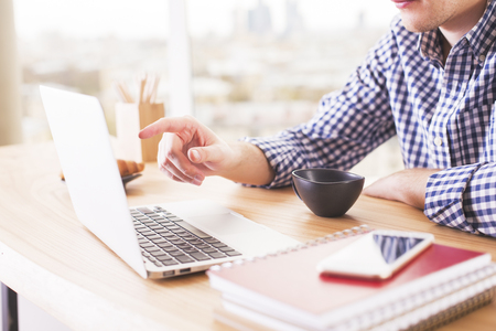 screen: Sideview of caucasian male pointing at laptop screen with finger on blurry city background Stock Photo