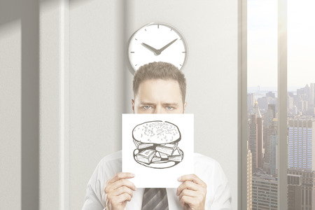 Frowny businessman cant wait for lunch break, holding hamburger sketch in office interior with clock and city view. 3D Rendering