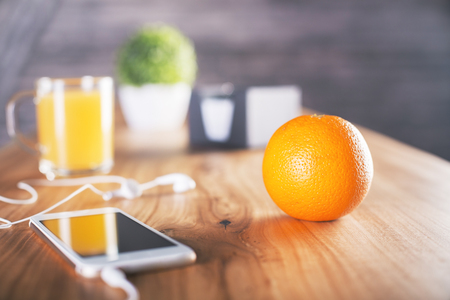 lunch table: Closeup of an orange on wooden desktop with smartphone and headphones, cup with juice and other items