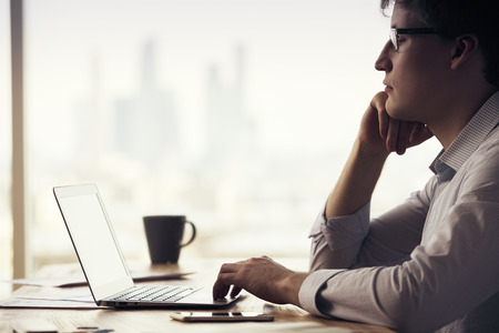 businessman thinking: Sideview of thinking caucasian businessman sitting at office desk with laptop, smartphone and coffee cup on blurry city background Stock Photo