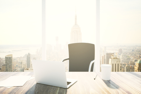 workspace: Desktop with laptop and coffee cup in office interior with New York city view. 3D Rendering