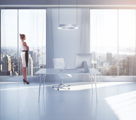 looking at view: Businesswoman looking outside of window in bright office interior with workplace and New York city view. 3D Rendering