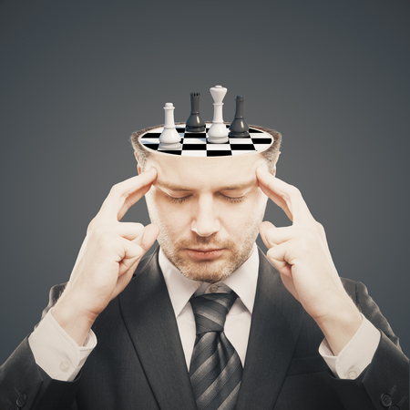 open minded: Thoughtful businessman with chess board instead of brain on grey background. Brainstorming concept