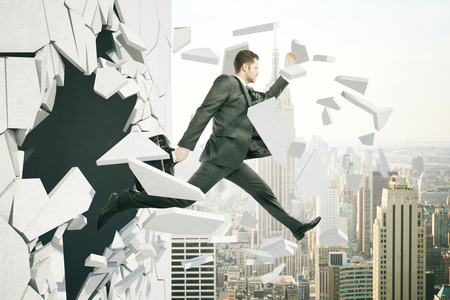 broken through: Business breakthrough success concept with man jumping through wall on city background Stock Photo