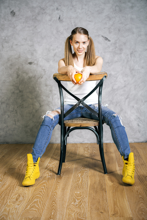 ponytails: Pretty girl with ponytails holding orange and sitting on a chair backwards Stock Photo