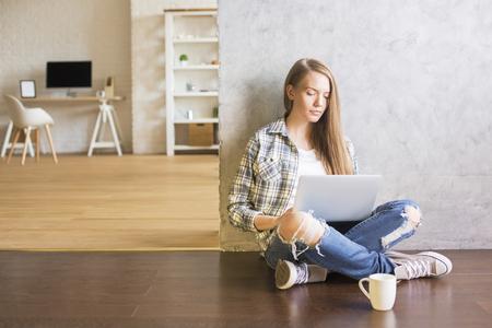 Fille assise sur un plancher en bois avec du café à l'intérieur et en utilisant un ordinateur portable