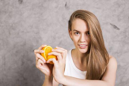 swept: Beautiful female with side swept hair holding orange halves on concrete background