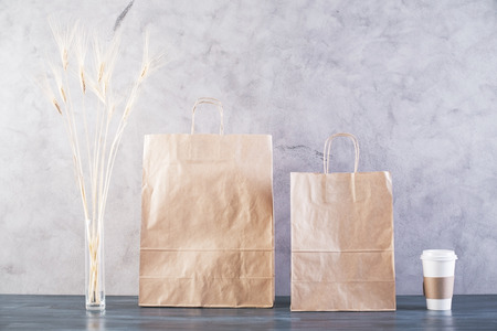 reusable: Two take away food bags, wheat spikes and coffee cup on concrete background. Mock up