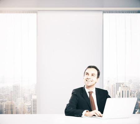 persona feliz: hombre de negocios con ordenador portátil sentado en la oficina con vista a la ciudad y la pared en blanco y pensando en algo sonriendo. Maqueta, 3D