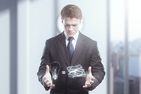 lightbulbs: Businessman with lightbulb as idea concept symbol and pile of money Stock Photo
