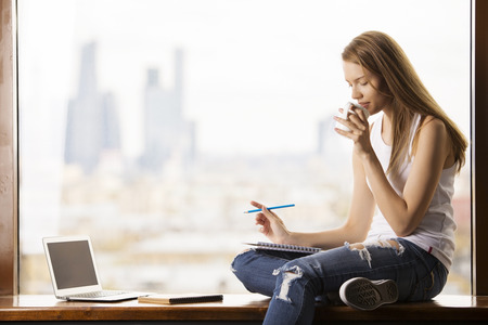 Young woman sitting on windowsill with blank laptop screen, drinking coffee and reading notes in notepad. Blurry city view in the background. Mock up