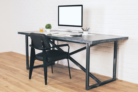 designer chair: Sideview of designer desk with blank white computer screen and black chair next to it on wooden floor and brick background. Mock up