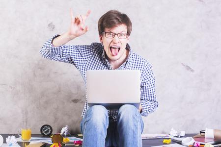 oficina desordenada: Hombre loco con la computadora port�til que se sienta en el escritorio de oficina desordenada y que muestra signo de los cuernos del diablo