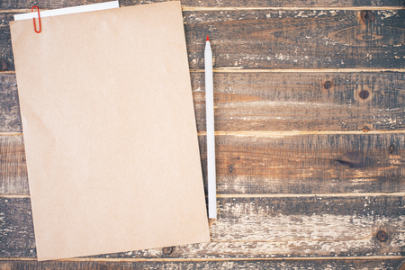 pencil and paper: Top view of blank brown paper and pencil on aged wooden desktop. Mock up