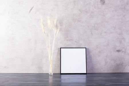 leaning: Small picture frame and wheat spikes on concrete background. Mock up Stock Photo