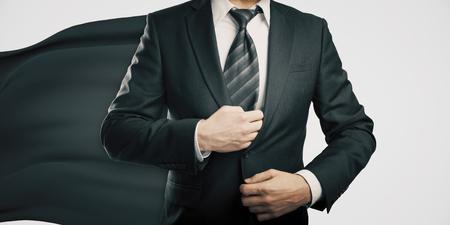 invincible: Businessman with black superhero cape on light background Stock Photo