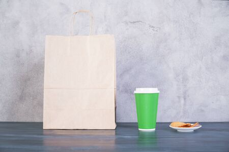 take away: Front view of blank take away food bag, cookies on saucer and green coffee cup on wooden surface and concrete background. Mock up Stock Photo