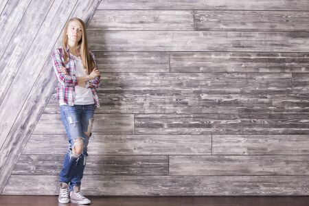 girl looking up: Casually dressed young woman with something on her mind standing against wooden plank wall. Mock up