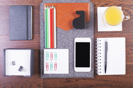 neatly: Top view of wooden desktop with neatly organized office tools, orange juice and smartphone. Mock up