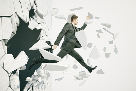 Business breakthrough success concept with businessman jumping through wall on white background