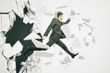 Zakelijke doorbraak succes concept met zakenman springen door de muur op een witte achtergrond