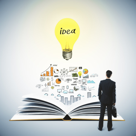 idea sketch: Idea concept with thinking businessman, book, light bulb and business sketch on grey background Stock Photo