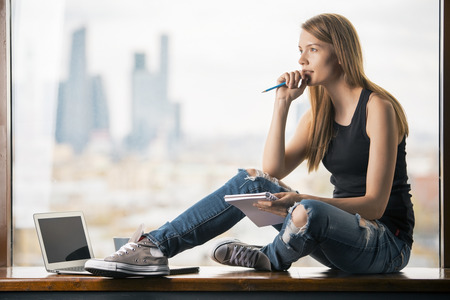 Thoughtful young woman with notepad in hand sitting on windowsill with blank laptop screen. Blurry city view in the background. Mock up