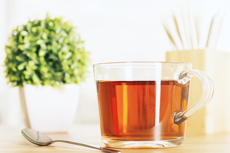 teaspoon: Wooden desktop with cup of tea, teaspoon and small plant Stock Photo