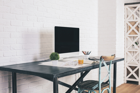 designer chair: Sideview of designer desk with blank computer screen and antique chair next to it on white brick wall background. Mock up Stock Photo