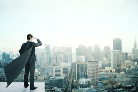 distance: Businessman with black superhero cape standing on pedestal and looking into the distance on cityscape background