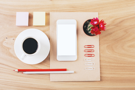 neatly: Top view of wooden desktop with blank white smartphone, coffee cup, cactus and stationery. Neatly organized. Mock up