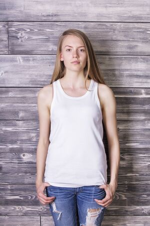 Attractive young woman wearing plain white tank top and jeans on wooden plank background. Mock up