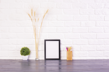 frame wall: Blank picture frame, pencil holder, plant and wheat spikes on wooden desktop and white brick wall background. Mock