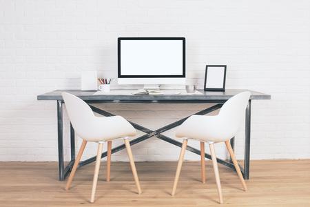 silla: Dos sillas junto a la mesa de diseño con pantalla en blanco y otros artículos en suelo de madera y fondo de ladrillo. Bosquejo Foto de archivo