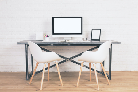 designer chair: Two chairs next to designer table with blank white computer screen and other items on wooden floor and brick background. Mock up